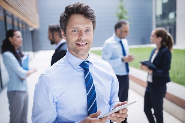 Ufny biznesmen trzyma cyfrową pastylkę na zewnątrz budynku biurowego