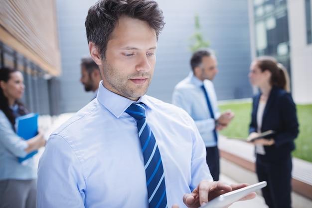 Ufny biznesmen używa cyfrową pastylkę na zewnątrz budynku biurowego