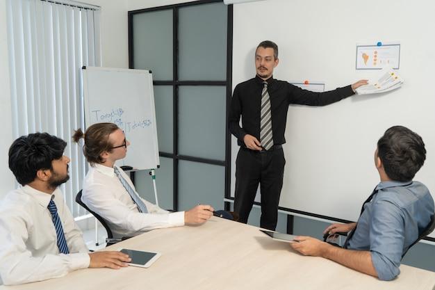 Ufny biznesmen wskazuje przy raportowym dokumentem z wąsem.