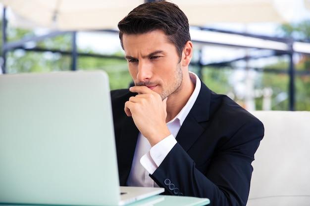 Ufny biznesmen za pomocą laptopa w restauracji