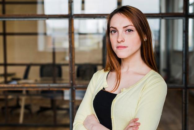 Ufny bizneswoman patrzeje kamerę z ręką krzyżującą