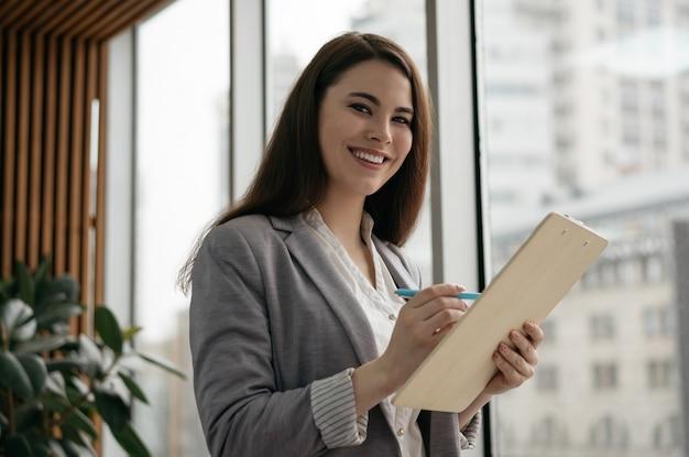 Ufny bizneswoman pracuje w nowożytnym biurze, robi notatkom, patrzeje kamerę, ono uśmiecha się