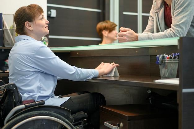 Ufny bizneswoman w wózku inwalidzkim przy biurem