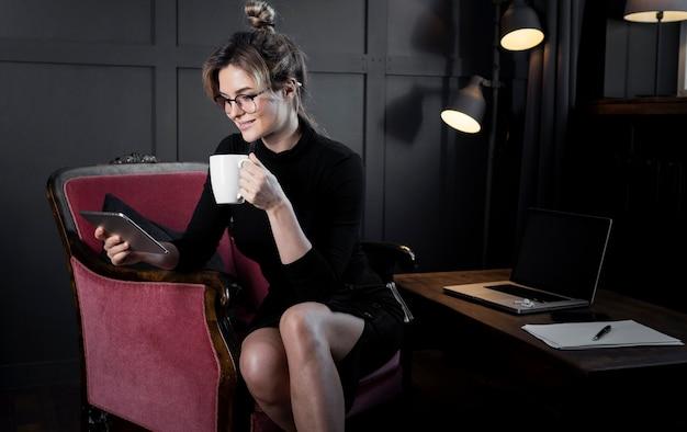 Ufny bizneswoman wyszukuje pastylkę przy biurem