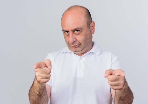 Ufny dojrzały biznesmen patrząc na przód i robi ci gest na białej ścianie