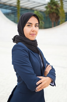 Ufny dumny muzułmański bizneswoman pozuje outside