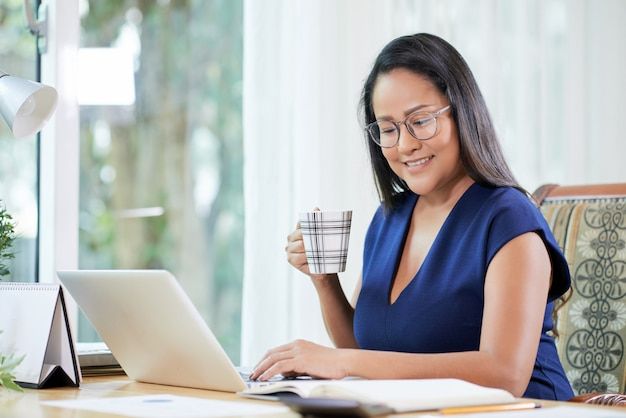 Ufny etniczny bizneswoman z kawą przy miejscem pracy