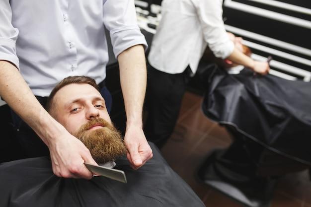 Ufny mans odwiedzający fryzjerki w sklepie fryzjerskim.