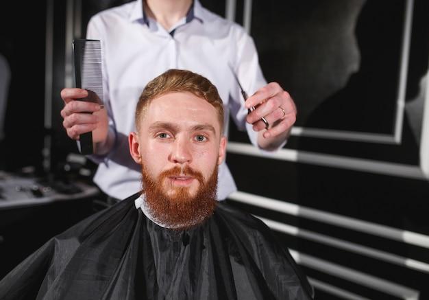 Ufny mężczyzna odwiedza fryzjerkę w fryzjera męskiego sklepie.