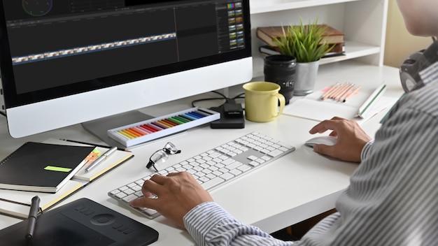 Ufny mężczyzna redaguje materiał na kreatywnym miejscu pracy