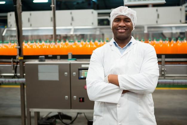 Ufny mężczyzna robotnik stojący w fabryce soku