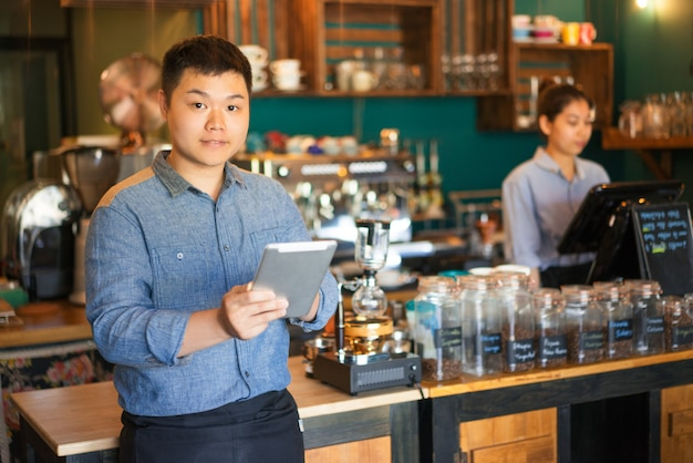 Ufny młody azjatycki męski kelner stoi przy kontuarem i używa touchpad w sklep z kawą