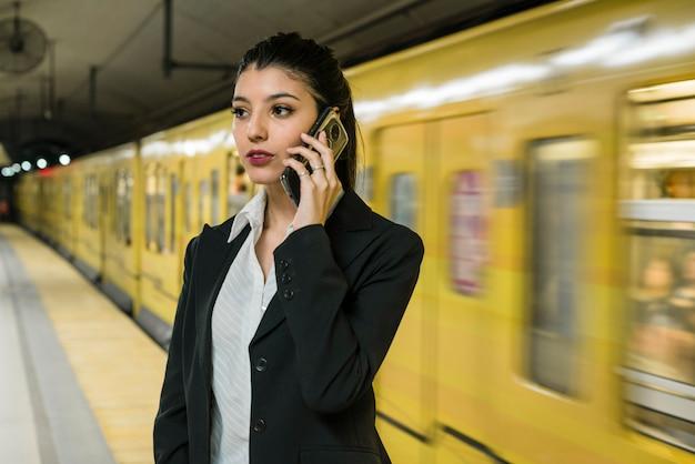 Ufny młody biznesmen opowiada na telefon komórkowy pozyci blisko poruszającego koloru żółtego pociągu