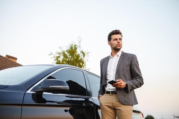 Ufny młody biznesmen w kostium pozyci przy jego samochodem