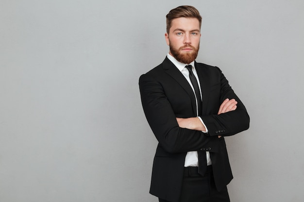 Ufny młody biznesmen w kostium pozyci z rękami składać