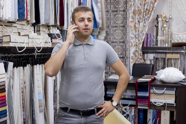 Ufny młody biznesmen, właściciel sklepu z tkaninami rozmawia przez telefon
