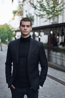 Ufny młody człowiek chodzi na europejskiej miasto ulicie