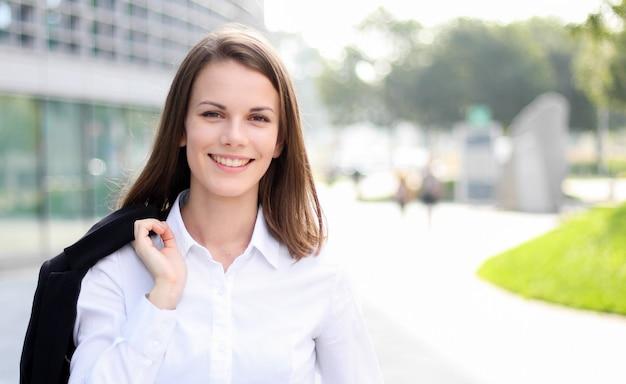 Ufny młody żeński kierownik plenerowy w nowożytnym miastowym położeniu