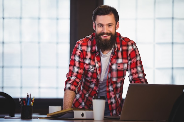 Ufny modniś opiera na biurku w kreatywnie biurze