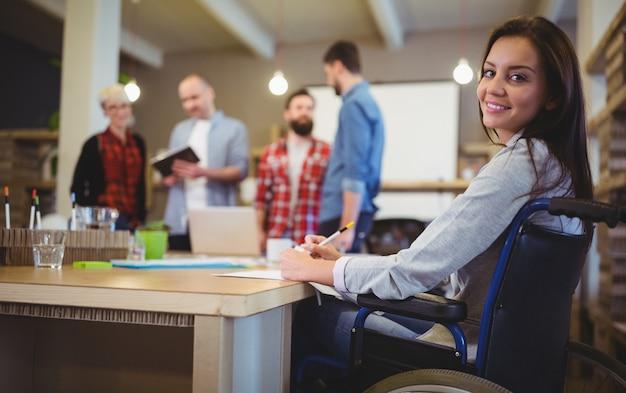 Ufny niepełnosprawny bizneswomanu writing przy biurkiem