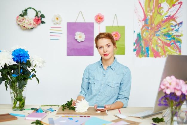 Ufny projektant kwiatów przy brudnym biurku