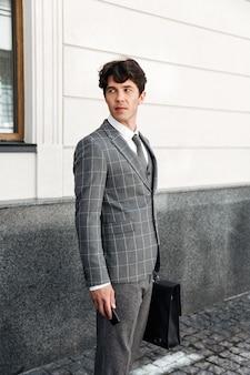 Ufny przystojny biznesmen trzyma kluczyki do samochodu w kostiumu