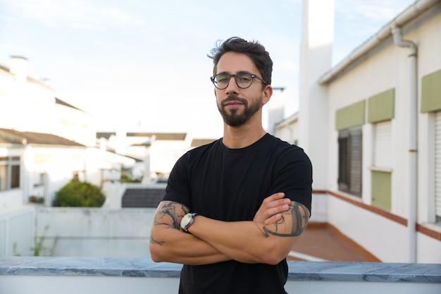 Ufny stylowy facet z tatuażami pozuje na balkonie mieszkania