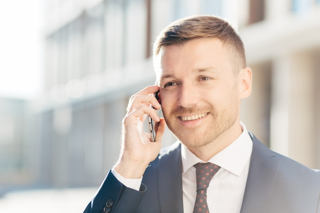 Ufny szczęśliwy biznesmen w średnim wieku komunikuje się przez telefon komórkowy