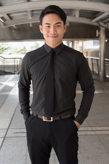 Ufny, szczęśliwy, odnoszący sukcesy azjatycki biznesmen