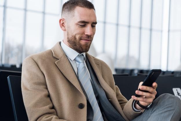 Ufny szef w luksusowym garniturze sprawdza pocztę elektroniczną za pomocą telefonu komórkowego przed spotkaniem z personelem
