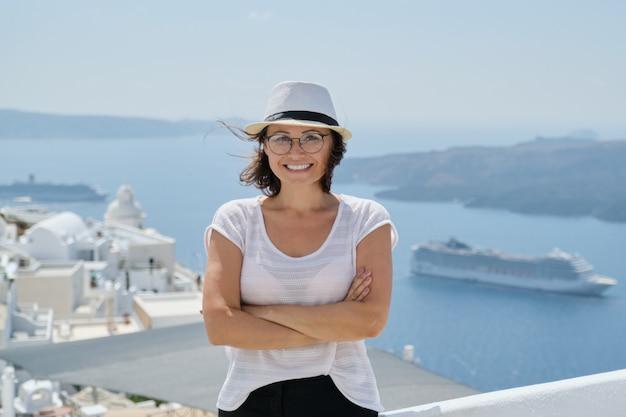Ufny uśmiechnięty kobieta turysta podróżuje na luksusowym rejsie w śródziemnomorskim, grecja, santorini