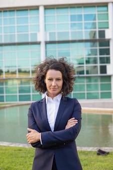 Ufny w średnim wieku bizneswoman pozuje blisko budynku biurowego