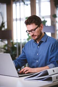 Ufny wykonawczy działanie na laptopie przy kreatywnie biurem