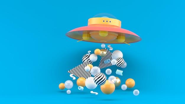 Ufo wśród kolorowych kulek na niebieskiej przestrzeni