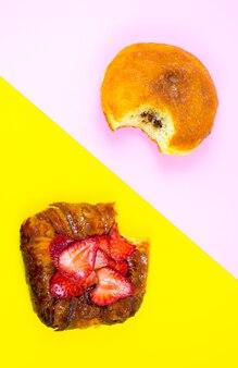 Ugryziony ciasto i pączek. pyszne pokusy słodyczy i deserów na różowym i żółtym tle.