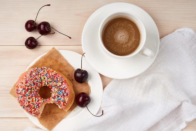 Ugryziony pączek, wiśnie na talerzu, filiżanka kawy z mlekiem, wysokokaloryczne śniadanie, widok z góry