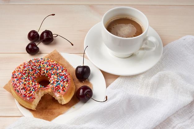 Ugryziony pączek, wiśnie na talerzu, filiżanka kawy z mlekiem, wysokokaloryczne śniadanie