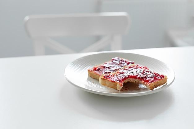 Ugryziony tost z dżemem na stole. spóźniony do pracy nie miał czasu zjeść śniadania
