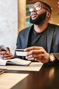 Ujęcie afroamerykańskiego biznesmena trzymającego telefon komórkowy i kartę kredytową podczas odpoczynku w kawiarni