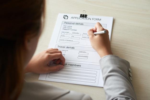 Ujęcie anonimowej kobiety przez ramię wypełniające formularz zgłoszeniowy