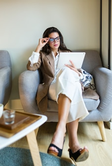 Ujęcie atrakcyjnej młodej bizneswoman za pomocą jej cyfrowego tabletu w kawiarni.