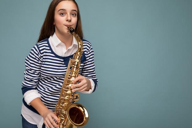 Ujęcie atrakcyjnej pozytywnej szczęśliwej brunet małej dziewczynki noszącej stylowy pasiasty longsleeve stojący