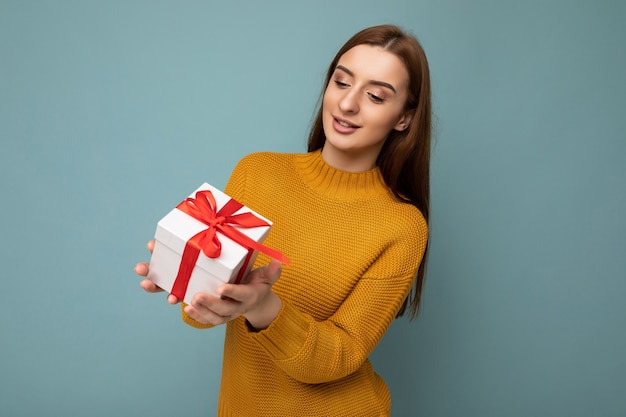 Ujęcie atrakcyjnej pozytywnej uśmiechnięta młoda brunetka kobieta samodzielnie nad kolorową ścianą na sobie codzienny modny strój trzymając pudełko i patrząc w bok.