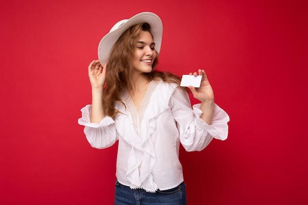 Ujęcie atrakcyjnej pozytywnej uśmiechniętej młodej ciemnej blondynki w białej bluzce i białym kapeluszu