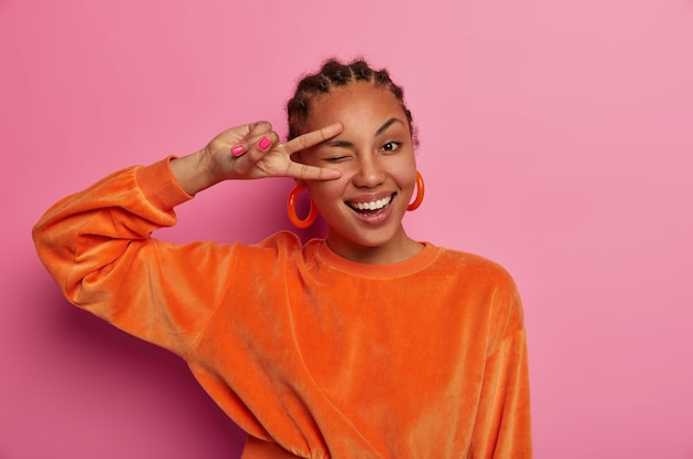 Ujęcie atrakcyjnej, wesołej kobiety wykonuje gest zwycięstwa, mruga okiem i uśmiecha się szeroko, cieszy się niesamowitą imprezą, wygłupia się i jest optymistą, wyraża pozytywne emocje, nosi pomarańczowe ubrania