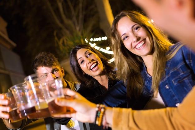 Ujęcie atrakcyjnych młodych przyjaciół opiekania z piwem na rynku jedzenia na ulicy.