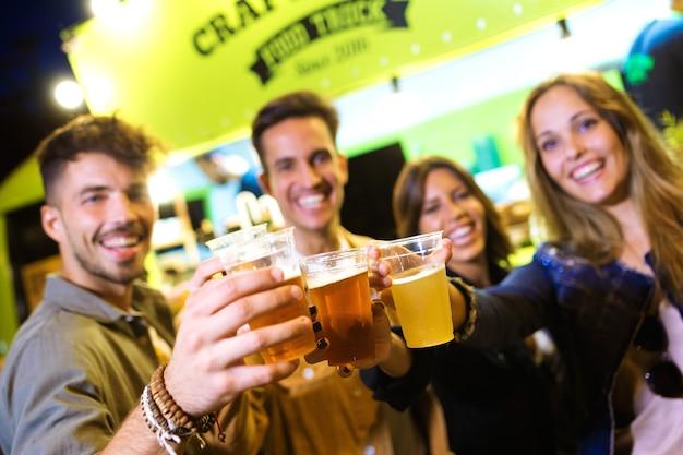 Ujęcie atrakcyjnych młodych przyjaciół patrząc na kamery podczas opiekania z piwem na rynku jedzenia na ulicy.