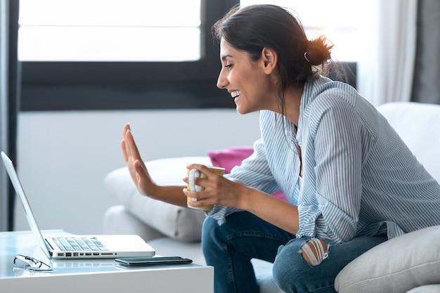 Ujęcie biznesowej kobiety machającej podczas rozmowy wideo online za pośrednictwem komputera przenośnego i zdalnej pracy z domu.