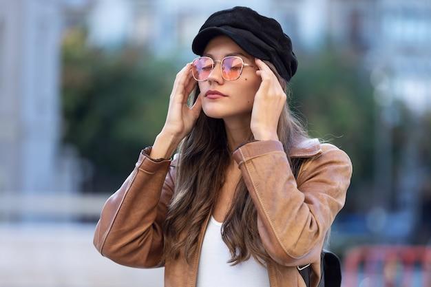 Ujęcie bolesnej młodej kobiety cierpiącej na ból głowy, stojąc na ulicy.