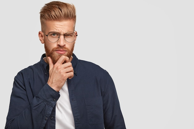 Ujęcie brutalnego, poważnego rudego mężczyzny z gęstą brodą, trzymającego brodę, unoszącego brwi, pogrążonego w myślach, kontemplującego coś, odizolowanego na białej ścianie